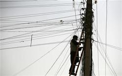 <p>An Afghan man repairs electricity cables along the streets of Kabul November 16, 2009. REUTERS/Jerry Lampen</p>