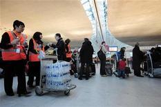 <p>Des employés d'Aéroports de Paris (ADP) distribuent des bouteilles d'eau à des passagers à l'aéroport Charles-de-Gaulle à Roissy, en région parisienne. L'opérateur des deux aéroports parisiens a accueilli en 2011 88,1 millions de passagers, un trafic record, en hausse de 5,7% par rapport à 2010. /Photo d'archives/REUTERS/Julien Muguet</p>