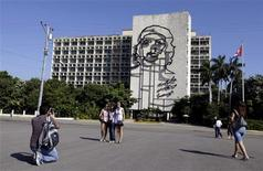 <p>Tourists take pictures in front of the Ministry of Interior (MININT) building displaying an image of revolution leader Che Guevara, in Havana's Revolution Square January 24, 2012. REUTERS/Enrique de la Osa</p>