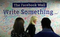 <p>People walk past the Facebook wall inside their office in New York December 2, 2011. REUTERS/Eduardo Munoz</p>