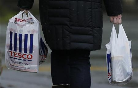 A Shopper carries bags as she leaves a Tesco store near Manchester, April 18, 2012. REUTERS/Phil Noble