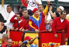 <p>El presidente venezolano, Hugo Chávez (al centro en la imagen), saluda a sus partidarios antes de inscribir su candidatura para los próximos comicios en Caracas, jun 11 2012. El presidente venezolano, Hugo Chávez, inscribió el lunes su candidatura a las elecciones de octubre, en las que buscará extender su mandato a casi 20 años, acompañado por cientos de miles de simpatizantes en su retorno a las calles tras una larga convalecencia por cáncer. REUTERS/Carlos Garcia Rawlins</p>