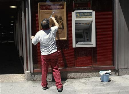 A man cleans a window of a bank branch in Madrid June 20, 2012. REUTERS/Andrea Comas