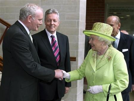 Britain's Queen Elizabeth shakes hands with Northern Ireland deputy first minister Martin McGuinness, watched by first minister Peter Robinson (C) at the Lyric Theatre in Belfast June 27, 2012. REUTERS/Paul Faith/pool