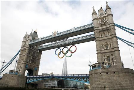 The Olympic Rings are seen hanging from Tower Bridge after being lowered into position for display from the walkways in central London, June 27, 2012. REUTERS/Andrew Winning