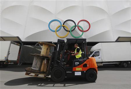 A worker drives a fork lift past Olympic Rings above an entrance to the Basketball Arena in the London 2012 Olympic Park at Stratford in London July 12, 2012. REUTERS/Luke MacGregor