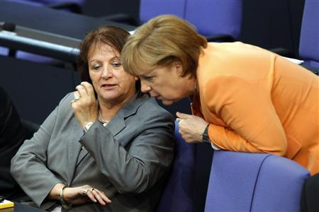 German Chancellor Angela Merkel (R) and Justice Minister Sabine Leutheusser-Schnarrenberger talk during a debate about a proposed resolution on circumcision in Berlin, July 19, 2012. REUTERS/Thomas Peter