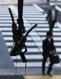 <p>Foto de archivo de unos transeúntes junto a una gasolinera en Tokio, mar 15 2012. Los precios del petróleo Brent cayeron el miércoles a mínimos de seis semanas, a medida que el mercado asimilaba el anuncio de Arabia Saudita, el mayor exportador mundial de crudo, de que tomaría medidas para mantener controlados los valores, lo que generó expectativas de un incremento en la oferta. REUTERS/Toru Hanai</p>