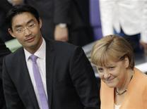 <p>Angela Merkel aux côtés du ministre allemand de l'Economie. Philipp Rösler a déclaré dans un communiqué que l'Allemagne avait réduit sa prévision de croissance pour 2013 à 1,0% au lieu de 1,6%, en invoquant la crise de la dette dans la zone euro et le ralentissement de la croissance dans les pays émergents. /Photo prise le 19 juillet 2012/REUTERS/Tobias Schwarz</p>