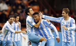 <p>Eliseu (deuxième à droite) félicité par Javier Saviola (à gauche) et Joaquin de Malaga. Malaga, qui fait cette année ses débuts en Ligue des champions, est qualifié pour les huitièmes de finale, sans attendre la fin de la phase de groupes. Le club a fait match nul face au Milan AC (1-1), mais totalise dix points dans sa poule. /Photo prise le 6 novembre 2012/REUTERS/Alessandro Garofalo</p>