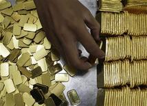 <p>Les cours de l'or poursuivent leur baisse et ont atteint leur plus bas niveau en un mois à 1.683,79 dollar l'once, le recul du taux de chômage aux Etats-Unis ayant fait grimper le dollar et atténué les spéculations autour de l'adoption par la Fed de mesures d'assouplissement monétaires supplémentaires. /Photo prise le 13 juillet 2012/REUTERS/Beawiharta</p>