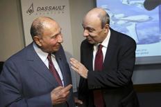 Le PDG de Dassault Aviation, Eric Trappier (à droite), s'entretient avec le sénateur UMP Serge Dassault, prpopriétaire du groupe qui porte son nom, avant la présentation des résultats 2013. L'avionneur a annoncé jeudi prévoir une baisse de son chiffre d'affaires en 2014, dans un secteur des jets encore convalescent qui l'oblige à prévoir une baisse de ses livraisons de Falcon. /Photo prise le 13 mars 2014/REUTERS/Philippe Wojazer