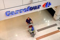 Vers 12h20, Carrefour grimpe de 1,23% quand  le CAC 40, lui, gagne 1,13% à 4.393,33 points. Moody's Investors Service a relevé mardi de stable à positive la perspective de la note à long terme du groupe, confirmée à Baa2. /Photo d'archives/REUTERS/Charles Platiau