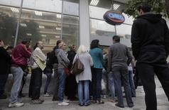 Des Grecs forment une file d'attente devant l'entrée d'une agence pour l'emploi à Athènes. Le taux de chômage en Grèce est revenu à 26,7% en janvier, au plus bas depuis près d'un an mais encore proche de son record de 27,7% d'octobre 2013. /Photo d'archives/REUTERS/John Kolesidis