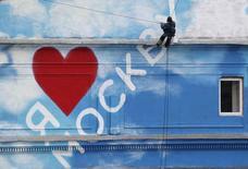 """Человек на тросе у стены с надписью """"Я люблю Москву"""" в Москве 8 октября 2013 года. Пришедшее в Москву на выходных потепление не оставит столицу в течение рабочей недели, позволив воздуху еще немного прогреться, ожидают синоптики. REUTERS/Sergei Karpukhin"""