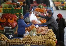 Мужчина продает овощи на рынке в Анкаре 5 февраля 2014 года. Всемирная торговая организация (ВТО) повысила прогноз роста мировой торговли до 4,7 процента с сентябрьской оценки в 4,5 процента, но предупредила, что не ожидает возвращения роста к историческому среднему уровню 5,3 процента ранее 2015 года. REUTERS/Umit Bektas
