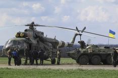 Украинские военные у вертолета Ми-8 на посту у города Изюм 15 апреля 2014 года. Два вертолета с военными сели на заблокированном пророссийскими сепаратистами аэродроме в Краматорске на востоке Украины, сообщил корреспондент Рейтер с места событий. REUTERS/Dmitry Madorsky