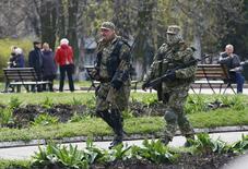 Пророссийские активисты идут по улице Славянска 14 апреля 2014 года. Между российской интервенцией в Крыму и событиями, разворачивающимися на этой неделе на востоке Украины, есть большая разница, позволяющая предположить, что Москва адаптировала разыгранный в Крыму сюжет и может рассчитывать на иной эффект.  REUTERS/Gleb Garanich