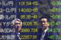 Мужчины стоят перед экраном с курсами валют и фондовыми котировками в Токио 14 апреля 2014 года. Курс иены к доллару снизился до 10-дневного минимума после выхода американской статистики и переговоров о ситуации на Украине. REUTERS/Issei Kato