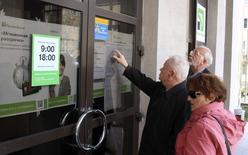 Devant une agence de la PrivatBank en Crimée. La Banque centrale de Russie a annoncé lundi qu'elle avait interdit à plusieurs banques ukrainiennes, dont la Privatbank, la Vseukrainsky Aktsionerny Bank, la banque Kyivska Rus et l'Imexbank, de travailler en Crimée, rattachée le mois dernier à la Fédération de Russie. /Photo prise le 4 avril 2014/REUTERS/Stringer