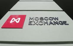 Логотип и вывеска у входа в помещение Московской биржи 14 марта 2014 года. Российский рынок акций, открывшись умеренным снижением основных индексов, так и провел торговый день примерно на тех же уровнях, немного усилив снижение к закрытию. REUTERS/Maxim Shemetov