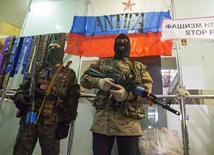 Пророссийские сепаратисты охраняют захваченный офис СБУ в Луганске 21 апреля 2014 года. Пророссийские сепаратисты на востоке Украины, разоружения которых в совместном коммюнике потребовали Россия, Украина, США и ЕС, в понедельник встретились с представителями ОБСЕ, которым женевская четвёрка поручила контролировать воплощение в жизнь хрупкого соглашения. REUTERS/Stringer