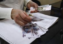 Кассир почтового отделения считает рубли, Симферополь, 25 марта 2014 года. Рубль подрос в начале биржевой сессии вторника перед ключевой для экспортеров уплатой НДПИ в пятницу. REUTERS/Shamil Zhumatov