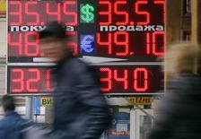 Люди проходят мимо пункта обмена валют в Москве 3 апреля 2014 года. Рубль снижается к бивалютной корзине и её компонентам на торгах пятницы в ответ на понижение суверенного рейтинга России агентством S&P и в условиях эскалации ситуации на востоке Украины. REUTERS/Maxim Shemetov
