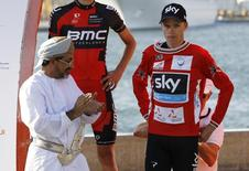 Team Sky rider Chris Froome (R) of Britain puts on the leader's red jersey after winning the Tour of Oman cycling race before the podium ceremony in Muscat February 23, 2014. REUTERS/Hamad I Mohammed