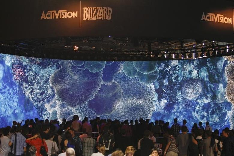 Visitors look at a presentation at the ActiVision Blizzard exhibition stand during the Gamescom 2013 fair in Cologne August 21, 2013. REUTERS/Ina Fassbender/Files