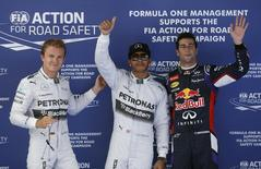 Mercedes Formula One driver Lewis Hamilton (C) of Britain gestures after taking the pole position, accompanied by second-fastest teammate Nico Rosberg (L) of Germany and third-fastest Red Bull Formula One driver Daniel Ricciardo (R) of Australia, at the qualifying session of the Spanish F1 Grand Prix at the Barcelona-Catalunya Circuit in Montmelo May 10, 2014. REUTERS/Albert Gea