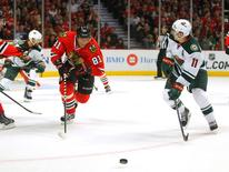 May 11, 2014; Chicago, IL, USA; Chicago Blackhawks right wing Marian Hossa (81) and Minnesota Wild left wing Zach Parise (11) skate for the puck during the third period of game five of the second round of the 2014 Stanley Cup Playoffs at the United Center. Chicago won 2-1. Mandatory Credit: Dennis Wierzbicki-USA TODAY Sports
