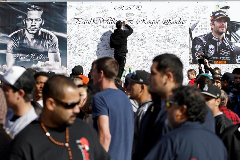 A man signs a large condolence card during an unofficial memorial event for ''Fast & Furious'' star Paul Walker in Santa Clarita, California December 8, 2013. REUTERS/Jonathan Alcorn/Files