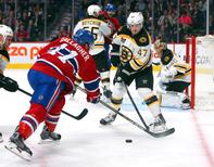 May 12, 2014; Montreal, Quebec, CAN; Montreal Canadiens right wing Brendan Gallagher (11) takes a shot on Boston Bruins goalie Tuukka Rask (40) and defenseman Torey Krug (47) during the third period in the game six of the second round of the 2014 Stanley Cup Playoffs at Bell Centre. Mandatory Credit: Jean-Yves Ahern-USA TODAY Sports