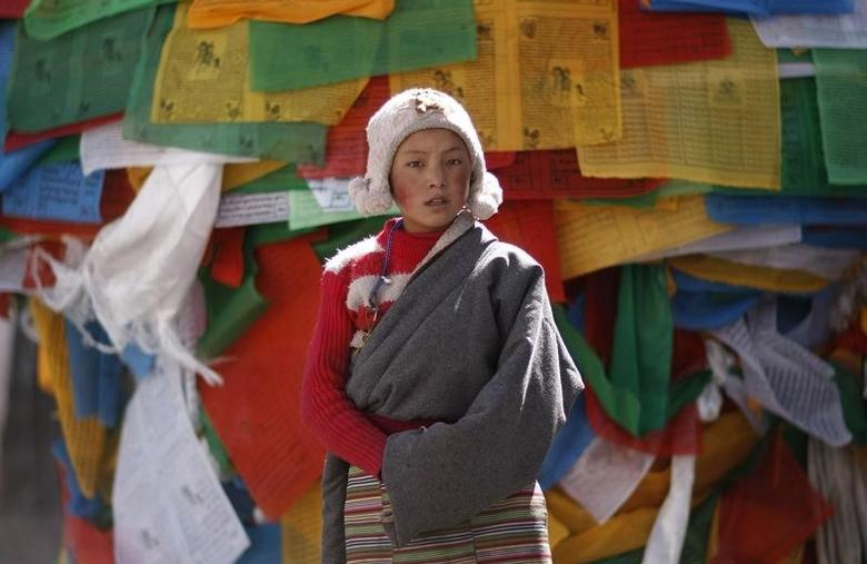 A girl stands in front of Tibetan prayer flags near Jokhang Monastery in Lhasa, Tibet autonomous region, March 7, 2014. REUTERS/Jacky Chen/Files