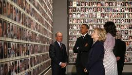 U.S. President Barack Obama (2nd L), former New York Mayor Michael Bloomberg (L), first lady Michelle Obama (2nd R), former U.S. President Bill Clinton (R) and his wife, former Secretary of State Hillary Clinton look at the faces of those who died during the 9/11 attacks, at the National September 11 Memorial Museum in New York May 15, 2014.  REUTERS/Kevin Lamarque