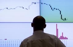 Сотрудник биржи РТС стоит у экрана с котировками и графиками в Москве 11 августа 2011 года. Российские фондовые индексы незначительно повысились на старте торгов пятницы, оставаясь в русле повышательной тенденции с начала мая. REUTERS/Denis Sinyakov