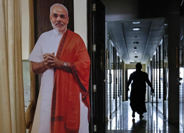 A party worker walks past a cut-out of Hindu nationalist Narendra Modi, the prime ministerial candidate for India's main opposition Bharatiya Janata Party (BJP), inside the party's regional office in Mumbai May 14, 2014. REUTERS/Danish Siddiqui