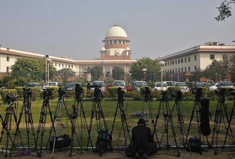 A television journalist sets his camera inside the premises of the Supreme Court in New Delhi February 18, 2014. REUTERS/Anindito Mukherjee/Files/Files