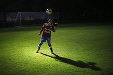 Daniela Pardo, captain of Chile's national women's soccer team, balances a ball on her head while training in Santiago May 14, 2014.  REUTERS/Ivan Alvarado