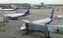 Самолёты Аэрофлота в аэропорту Шереметьево 24 июня 2013 года. Совет директоров Аэрофлота предлагает заплатить акционерам дивиденды за 2013 год в размере 2,4984 рубля на одну акцию, что в 2,15 раза превышает размер дивидендов за 2012 год. REUTERS/Sergei Karpukhin