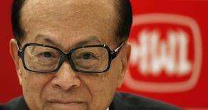 L'homme le plus riche d'Asie, Li Ka-shing, devant le logo du groupe qu'il dirige, Hutchison Whampoa. Les autorités européennes de la concurrence devraient approuver le projet de rachat de la filiale irlandaise de Telefonica par Hutchison Whampoa pour un milliard de dollars (730 millions d'euros) dès que le conglomérat de Hong Kong aura signé un accord avec le câblo-opérateur Liberty Globa. /Photo d'archives/REUTERS/Bobby Yip