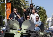 "(2ndL-R) Cast members Randy Couture, Arnold Schwarzenegger, Victor Ortiz, Glen Powell and Antonio Banderas pose on a tank as they arrive on the Croisette to promote the film ""The Expendables 3"" during the 67th Cannes Film Festival in Cannes May 18, 2014.       REUTERS/Yves Herman"