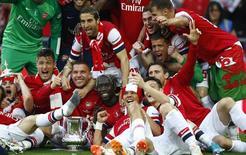 """Игроки """"Арсенала"""" радуются победе в Кубке Англии в Лондоне 17 мая 2014 года. Лондонский """"Арсенал"""" выиграл первый трофей за последние девять лет, в субботу в финале Кубка Англии одержав волевую победу над """"Халл Сити"""" в дополнительное время. REUTERS/Darren Staples"""
