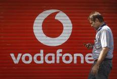 Мужчина проходит мимо магазина с логотипом Vodafone в Мумбаи 15 января 2014 года. Британская телекоммуникационная компания Vodafone отчиталась во вторник о результатах за минувший финансовый год, оказавшихся на уровне рыночных ожиданий, и заявила, что ждет сокращения базовой прибыли в 2014/2015 году из-за необходимости инвестиций. REUTERS/Danish Siddiqui