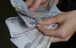 Продавец пересчитывает купюры на рынке в Москве 3 марта 2014 года. Рубль в среду продолжил укрепляться к доллару и бивалютной корзине, но текущая активность остается невысокой и будет снижаться по мере приближения знаковых выходных, когда должны пройти выборы президента Украины. REUTERS/Maxim Shemetov
