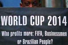 Manifestation à Rio de Janeiro contre l'organisation de la Coupe du monde de football au Brésil. Le pays a longtemps espéré que l'organisation de cette compétition sportive donnerait un élan supplémentaire à son économie, mais aujourd'hui, cet espoir a pour une bonne part laissé la place à la peur de voir les troubles sociaux effrayer les investisseurs et ternir pour longtemps l'image du Brésil. /Photo prise le 14 mai 2014/REUTERS/Sergio Moraes