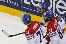 Tomas Rolinek of the Czech Republic (top) celebrates with his team mates Ondrej Vitasek (L) and Michal Vondrka after scoring against the U.S. during their men's ice hockey World Championship quarter-final game at Chizhovka Arena in Minsk May 22, 2014.   REUTERS/Vasily Fedosenko