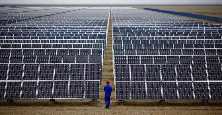 A worker inspects solar panels at a solar Dunhuang, 950km (590 miles) northwest of Lanzhou, Gansu Province September 16, 2013. REUTERS/Carlos Barria/Files
