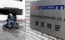Un moticiclista pasa por la entrada de la sede central de Hon Hai, que también es conocida por la marca Foxconn, en Tucheng, ciudad de Nueva Taipei. 24 diciembre, 2013. Foxconn Technology Group, el proveedor de Apple Inc, comprará una participación en el operador de comunicaciones móviles de Taiwán Asia Pacific Telecom por 11.600 dólares taiwaneses (390 millones de dólares) en un acuerdo que ampliaría su presencia en el creciente mercado de telecomunicaciones 4G de la isla.  REUTERS/Pichi Chuang